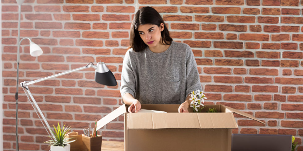 Frau räumt Schreibtisch leer, Karton