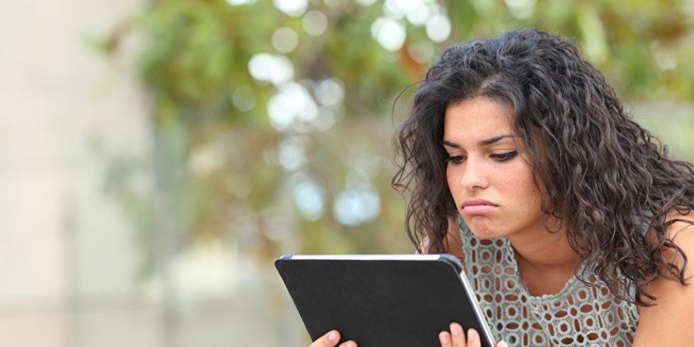 Frau schaut frustriert auf Tablet